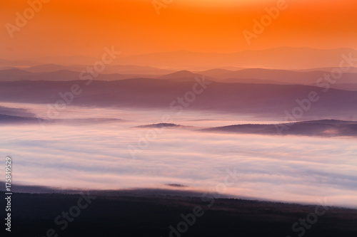 Staande foto Oranje eclat peaceful landscape with mountain range scenic view and morning fog on sunrise