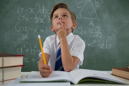 Schoolboy doing his homework in classroom