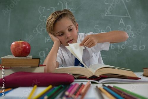 Schoolboy reading book in classroom