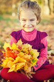 Happy little girl with autumn leaves in the park - 175854502
