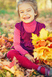 Happy little girl with autumn leaves in the park - 175854512