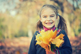 Portrait of happy little girl with autumn leaves in the park - 175854520