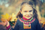 Portrait of happy little girl with autumn leaves in the park - 175854539