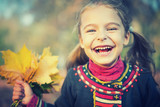Portrait of happy little girl with autumn leaves in the park - 175854553