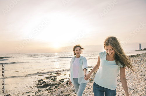 Poster Close up portrait of mom and her teenage daughter hugging and smiling together over sunset sea view