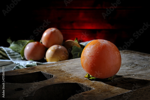 Fresh persimmons freshly picked on an old wooden table - 175860703