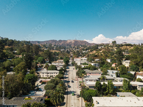 Hollywood sign district in Los Angeles, USA. Beautiful Hollywood highway road with cars, palms and a sign on the hills. Clear blue sky.