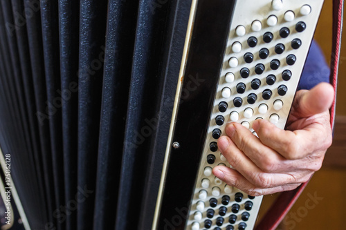 Póster Musician hand playing accordions closeup