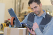 Quadro worker with trolley wheel reading the tablet