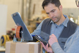 worker with trolley wheel reading the tablet - 175869943