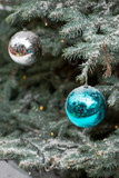 Close-up detail of multiple shiny blue and white ball ornaments hanging from a snow covered pale spruce tree with Christmas lights. Singapore. Vertical orientation. Travel and holidays concept.
