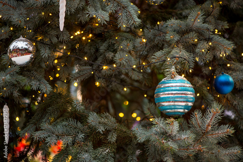 Wide angle detail of multiple ball and icicle-shaped ornaments of various colors and yellow Christmas lights on a pale spruce tree Poster