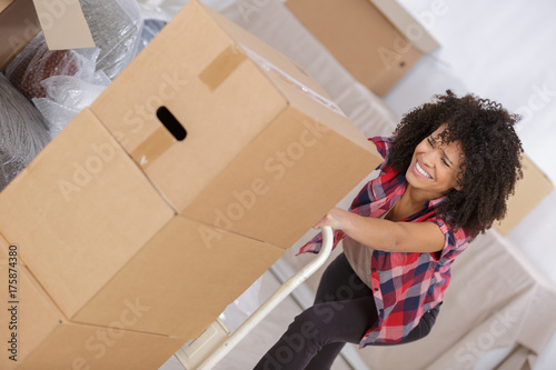 woman struggling carrying heavy carton box with furniture Poster