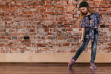 Hip hop for teenagers. Urban style. Modern young girl in studio, brick wall background with free space. Breakdance for life, movement concept