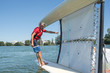 salior trying to right his catamaran after capsize