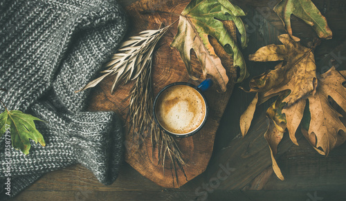 Autumn or Fall morning coffee concept. Flat-lay of arm knitted woolen grey sweater, wooden tray, mug of coffee and yellow fallen leaves over dark rustic wooden table background, top view