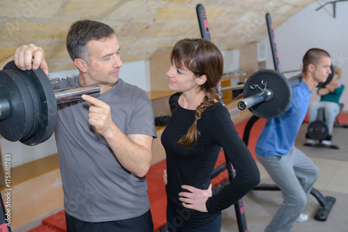 Fotobehang Fitness trainer explaining how to use training machine in a gym