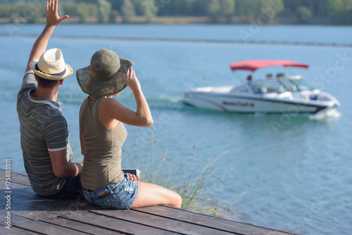couple sat on pier waving to passing boat