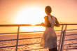 Cruise ship vacation woman travel watching sunset at sea ocean view. Elegant lady in white dress relaxing on deck balcony, luxury holiday destination. - 175886932