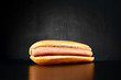 Plain hotdog with big sausage isolated on black background. Front view.