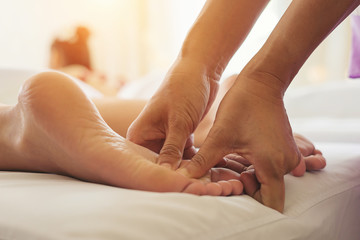 Close-up of woman doing foot massage at spa.