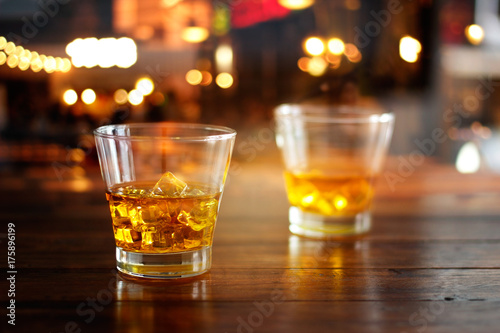 Whiskey glasses drink with ice cubes on wooden table in colorful night bar