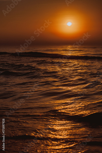 Fotobehang Strand Beatiful red sunset over sea surface