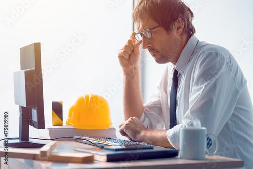 Construction engineer working on desktop computer using CAD soft