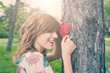 Cute girl holding heart - shape and hugging the tree.