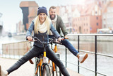 Young couple riding bikes and having fun in the city - 175904505