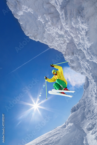 Skier jumping against blue sky from the rock - 175911597