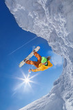 Snowboarder jumping against blue sky - 175911718