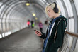 Young girl listens to music in big headphones in the subway