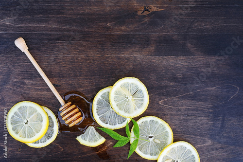 On a wooden texture background a lemon and honey Poster