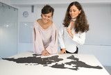 Twins girls fixing the world map on the table - 175919182