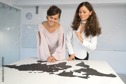 Twins girls fixing the world map on the table