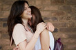 Two girls hugging. brick wall in background