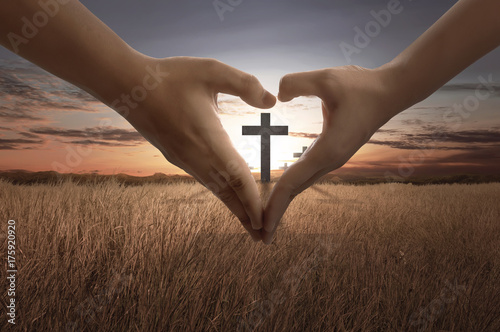 People hand making heart sign with bright cross inside Poster