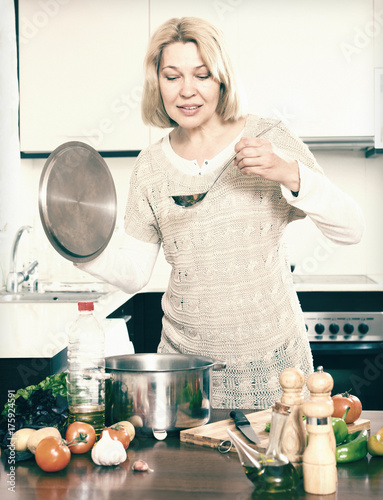 Happy  mature  housewife  with ladle cooking soup in pan  in kit Poster