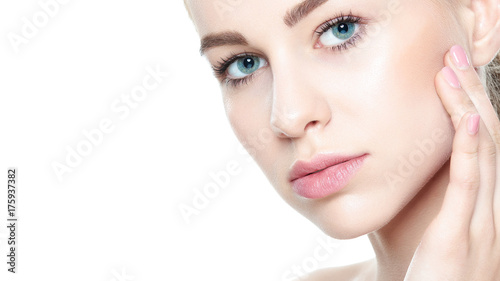 Beautiful Young Blond Woman with Perfect Skin touching her face. Facial treatment. Cosmetology, beauty and spa concept. Isolated on white background.