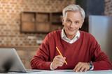 Cheerful senior engineer posing while drawing blueprint - 175940398