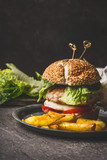 Homemade tasty burger with chicken, lettuce, mozzarella and tomatoes on rustic kitchen table background, front view - 175940979