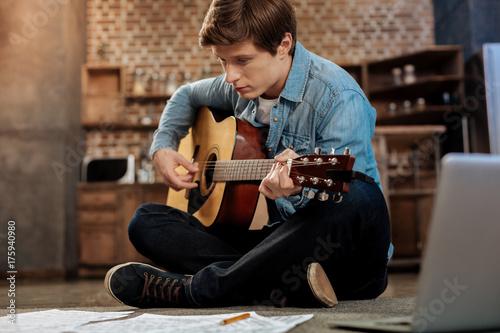 Póster Handsome man having guitar practice on the floor