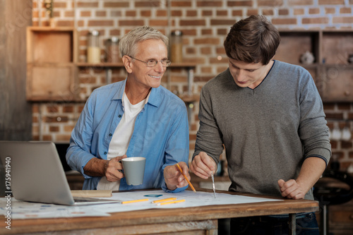 Pleasant mentor helping young colleague draw blueprint