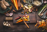 Colorful sliced carrots with knife on wooden cutting board on rustic kitchen table background with root vegetables ingredients for tasty vegetarian cooking, top view.  Healthy food and eating - 175944323