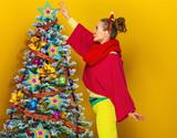 woman near Christmas tree on yellow background decorating - 175944339