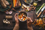 Female woman hands holding pan with diced colorful vegetables and a spoon on rustic kitchen table with vegetarian cooking ingredients and tools. Healthy and clean food  cooking and eating  concept. - 175944530