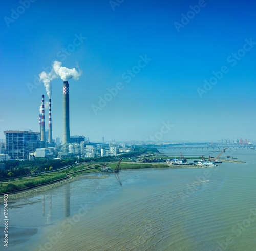 Smoking smokestack of chemical plant near gulf with blue sky Poster