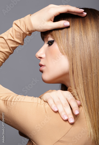 Keuken foto achterwand Kapsalon Portrait of blonde young woman. Female with green eyes and long hair. Girl dressed in beige dress on gray background.