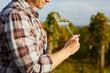 Man tasting white wine on vineyard in autumn